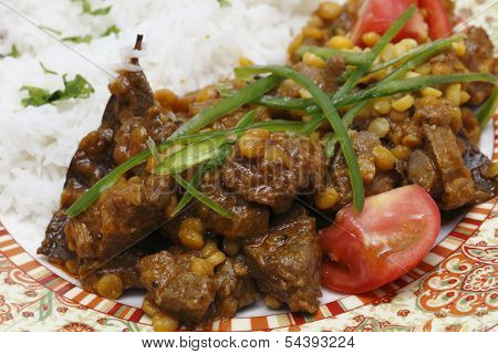 Lahore (Pakistan) style lamb and Chana dhal (split pea) curry, garnished with sliced chillies and chopped tomato, and served with white rice.