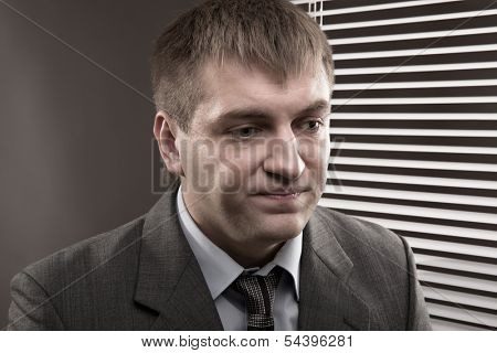 Frustrated young office worker looking down wearily