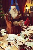 pic of letters to santa claus  - The messy desk of Santa Claus he reading a book on background - JPG
