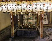 Fragment Of A Shinto Shrine With Purification Ladles, Sake Offerings And White Lanterns