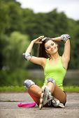 stock photo of inline skating  - Happy young girl enjoying roller skating rollerblading on inline skates sport in park - JPG