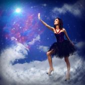 stock photo of reach the stars  - Young woman reaching for a glowing star - JPG