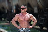 picture of lats  - Bodybuilder Showing His Front Lat Spread Outdoors At Railroad - JPG