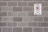 stock photo of cinder block  - No Parking sign on cement block wall - JPG