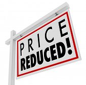 picture of reduce  - Price Reduced words on a home for sale sign to illustrate a home owner in distress and needing to sell immediately as a short sale or negotiated lower value to the right buyer - JPG