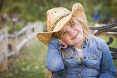 stock photo of baby cowboy  - Cute Smiling Young Girl Wearing Cowboy Hat Posing for a Portrait Outside - JPG