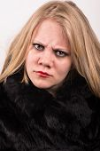 image of stubborn  - sour and stubborn young woman in a fur jacket stares into the camera with a white backround behind - JPG