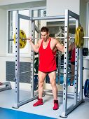 stock photo of squatting  - weightlifter squats with a barbell - JPG
