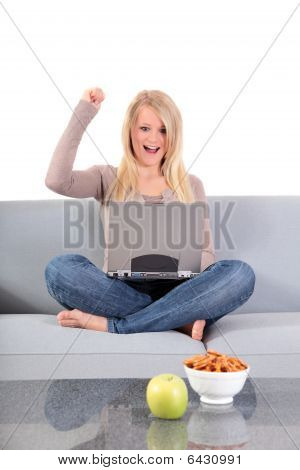 Cheering young woman surfing the internet