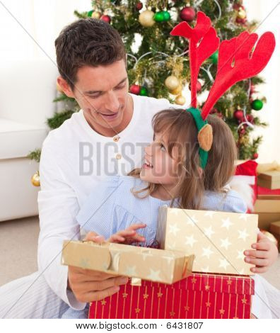 Portrait Of A Smiling Father And His Daughter Opening Christmas Presents