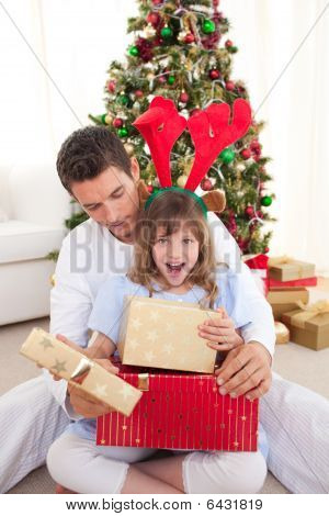 Surprised Little Girl Opening Presents With Her Father
