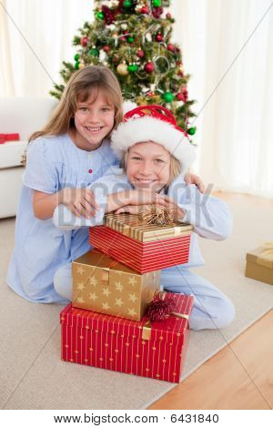 Happy Brother And Sister Holding Christmas Presents
