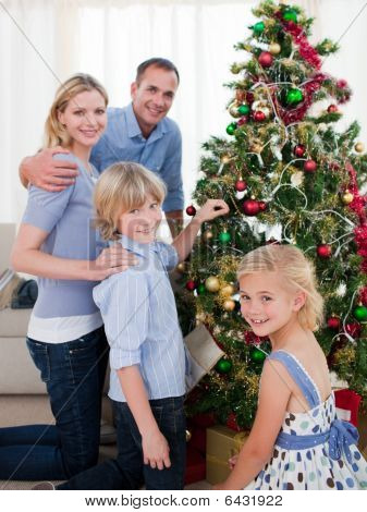 Portrait Of A Young Family Decorating A Christmas Tree