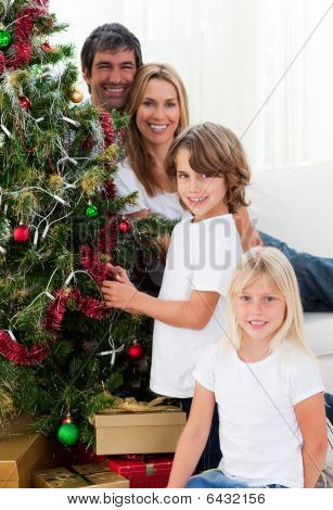 Portrait Of A Happy Family Decorating A Christmas Tree