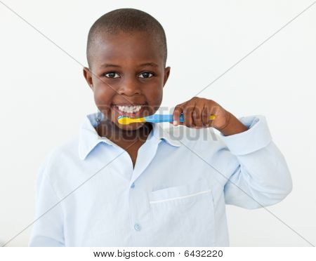 Portrait Of A Smiling Little Boy Brushing His Teeth
