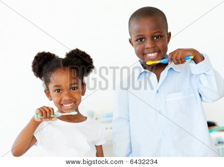 Smiling Brother And Sister Brushing Their Teeth