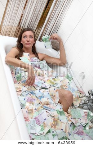 Happy Woman In A Bathtub Full Of Money