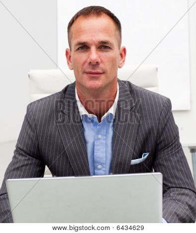 Portrait Of A Serious Businessman Using A Laptop