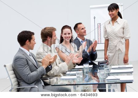 Businesswoman Applauding A Colleague After Giving A Presentation