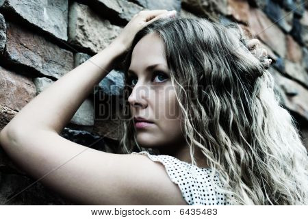 Sad Woman Against A Stone Wall.