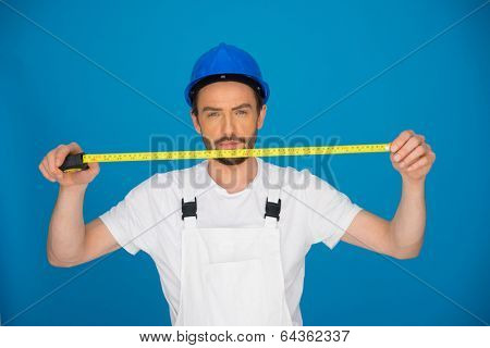 Young builder or workman in a hardhat and dungarees holding up a measuring tape extended in front of his face on a blue background