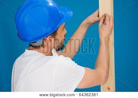 Carpenter or joiner marking a measurement with a pencil on a length of wood , view over his shoulder from behind, blue background