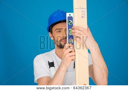 Young male carpenter or builder holding a spirit level and plank of wood in front of him on a blue background