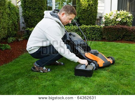 Mature Man Putting Battery Into Electric Lawn Mower