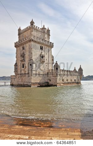 LISBON, PORTUGAL - SEPTEMBER 28, 2011: The famous Tower of Belem in water of river Tagus. White marble tower is decorated with turrets and battlements in the Moorish style