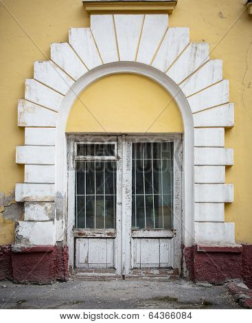 Low Wooden Window, With White Around The Arch Windows And Cracked Yellow Wall.