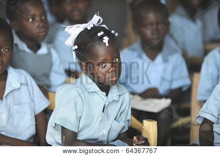 KOLMINY HAITI - FEBRUARY 12, 2014:    A young Haitian school crying girl in her classroom, surrounded by her classmates.  Shallow depth of field with focus on  tearful girl.