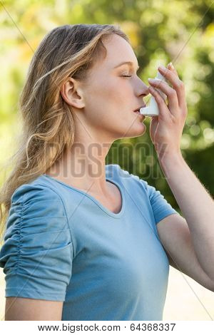 Side view of a young woman using asthma inhaler at the park