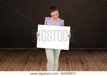 Pretty brunette showing card against dark room with floorboards