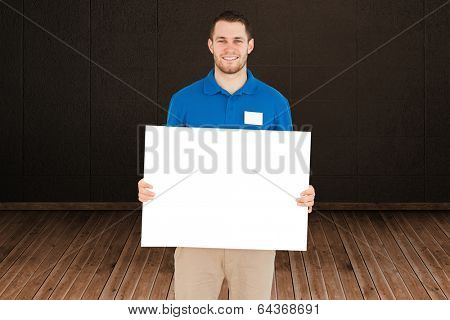 Handsome young man showing card against dark room with floorboards