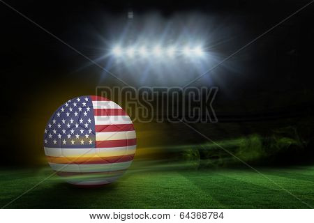 Football in america colours against football pitch under spotlights