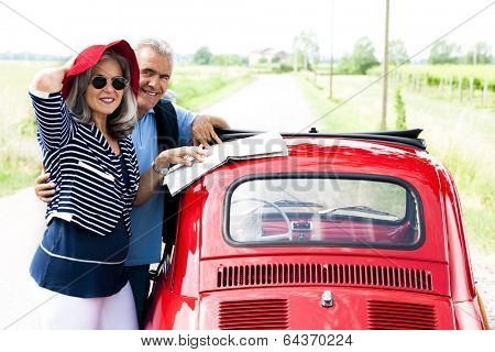 Senior couple with vintage car lookinga t a map