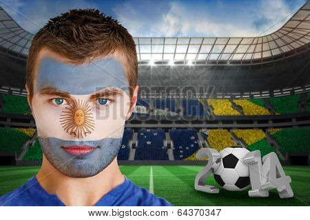 Composite image of serious young argentina fan with face paint against large football stadium with brasilian fans