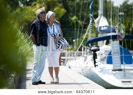 Happy senior couple walking on a dock in summer