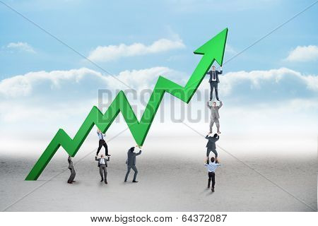 Business team holding up arrow against cloudy landscape background