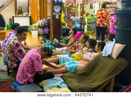 BANGKOK, THAILAND - MARCH 22: Thai masseur doing leg massage outdoors at the famous backpackers destination Khao San Road at night on March 22, 2014 in Bangkok, Thailand.