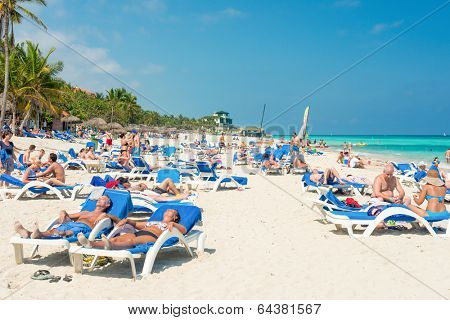 VARADERO,CUBA - APRIL 28,2014 : Tourists sunbathing and relaxing on a beautiful sunny day at the beach