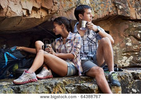 A couple relaxing by a cave and replenishing