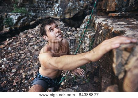 A handsome man with no shirt on rock climbing with copyspace