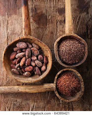 cocoa beans, hot chocolate flakes and grated dark chocolate in old texured spoons bowls on wood