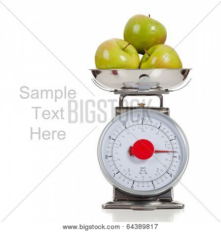 Green granny smith apples on a scale with a white background and copy space