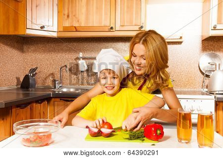 Smiling son cuts vegetables on table with mother