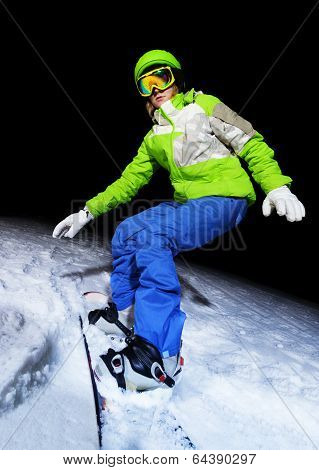 Portrait of girl balancing on snowboard at night