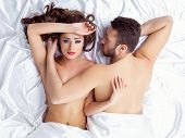 stock photo of lovers  - Image of weary young lovers posing lying on silk sheets - JPG