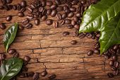 image of arabian  - Coffee beans and green leaves on wooden background  - JPG