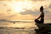 foto of  practices  - Silhouette of a young woman practicing yoga on the beach at sunrise - JPG